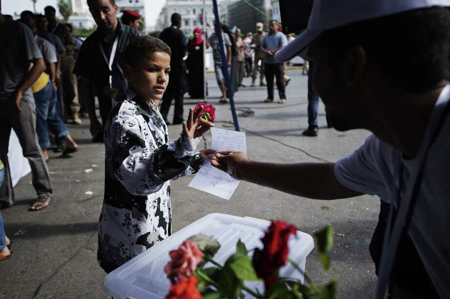 A Libyan child receives a flower after handing over a weapon in Tripoli's Martyrs' Square on Saturday. Hundreds of Libyans turned in weapons in the wake of rallies calling for the disarmament and disbanding of militias. Photo: GIANLUIGI GUERCIA / AFP ImageForum