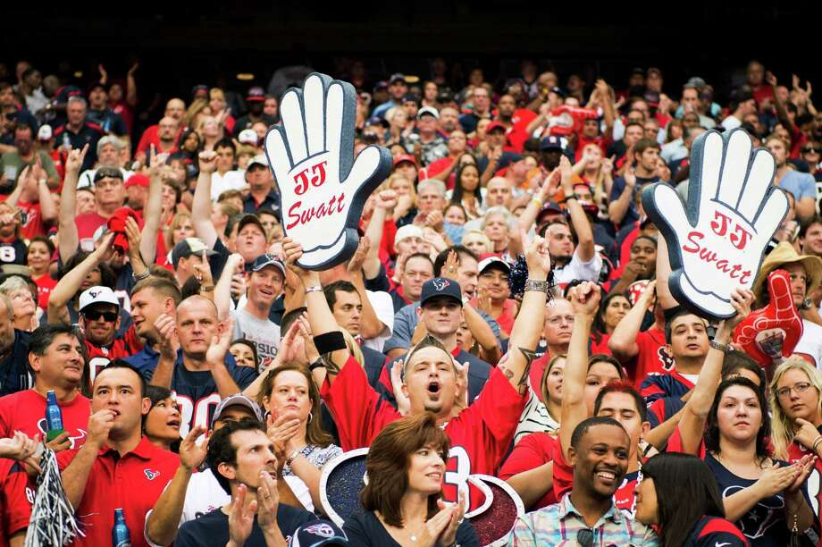By show of hands, a couple of fans in Sunday's crowd at Reliant Stadium declare their support for Texans second-year defensive end J.J. Watt. Watt had two sacks, upping his season total to 71/2, and also recovered a fumble. Photo: Smiley N. Pool / © 2012  Houston Chronicle