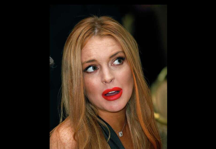 FILE - In this April 28, 2012 file photo, Lindsay Lohan attends the White House Correspondents' Association Dinner in Washington. A law enforcement official says a 25-year-old man got into an argument with Lohan, Sunday, Sept. 30, 2012, in her New York City hotel room over photos on a cellphone and she was physically grabbed or thrown. Authorities confirm that Christian LaBella of Valley Village, Calif., was taken into custody around 6 a.m. He faces a misdemeanor assault charge. (AP Photo/Haraz N. Ghanbari, File) Photo: Haraz N. Ghanbari / AP