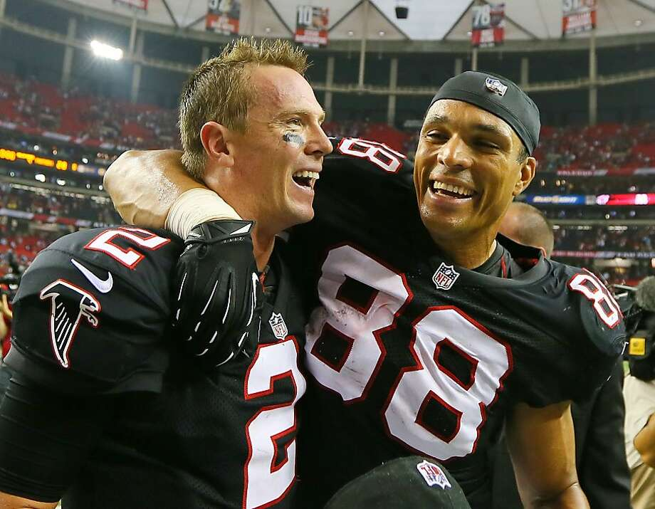 Quarterback Matt Ryan (2) and tight end Tony Gonzalez celebrate Atlanta's win over Carolina. Photo: Curtis Compton, Associated Press