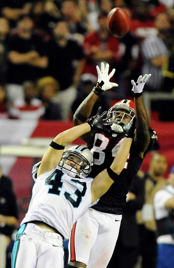 The Falcons' Roddy White goes above the Panthers' Haruki Nakamura to make a catch good for 59 yard and put Atlanta in position to kick the game-winning field goal. Photo: David T. Foster III / Charlotte Observer