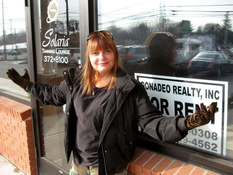 Michelle Bonanni stands outside the Solaria Tanning Lounge, 1055 Huntington Turnpike in Bridgeport. The tanning lounge closed abruptly in November, just days after she spent $158 to renew her membership. It has since been cleaned out to the bare walls, and Bonanni wonders when – or if – she'll get a refund. Photo: John Burgeson / Connecticut Post