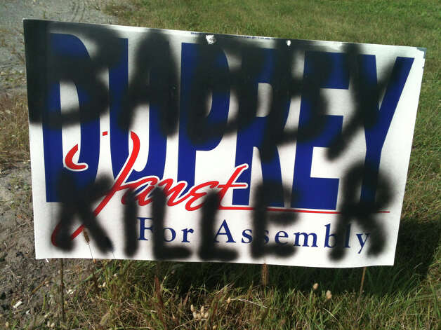 Assemblywoman Janet Duprey's campaign sign was defaced in September 2012. State Police are investigating for criminal mischief.