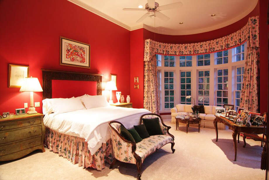 The master bedroom suite is dramatic with red walls and high windows. Photo: Daniel Zimmerman Real Estate Agency