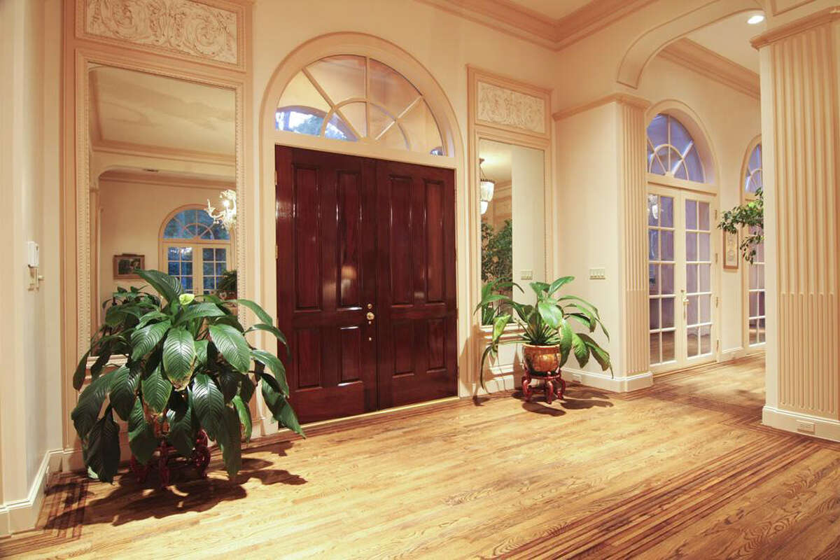 The grand foyer area features high ceilings and hardwood floors.