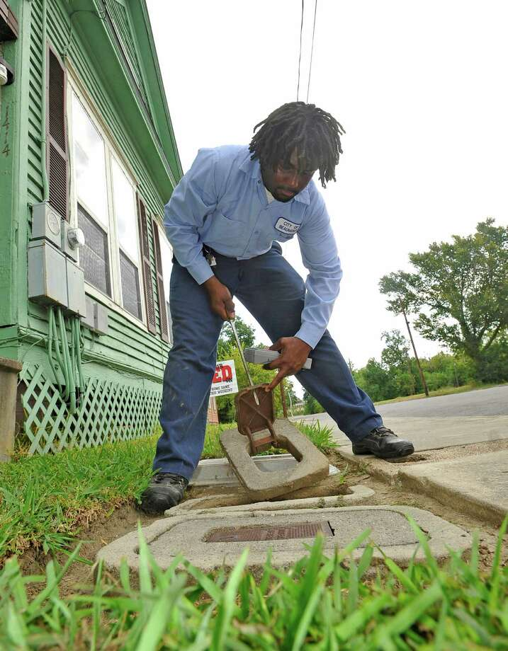 Alonzo Kinlaw, a city water meter reader, walked his route Thursday morning that included Magnolia and Gladys Streets, lifting water meter lids, and checking the numbers. In one location on Magnolia Street, three meters were all located in one place.  This is a job that will be going away in the next couple of years as the city replaces 29,000 old meters with radio transmitters. However, Kinlaw and his fellow meter readers, like Jackie Batiwste, will be shifted to other jobs in the water utilities or finance department because there will be a need for them. Dave Ryan/The Enterprise Photo: Dave Ryan