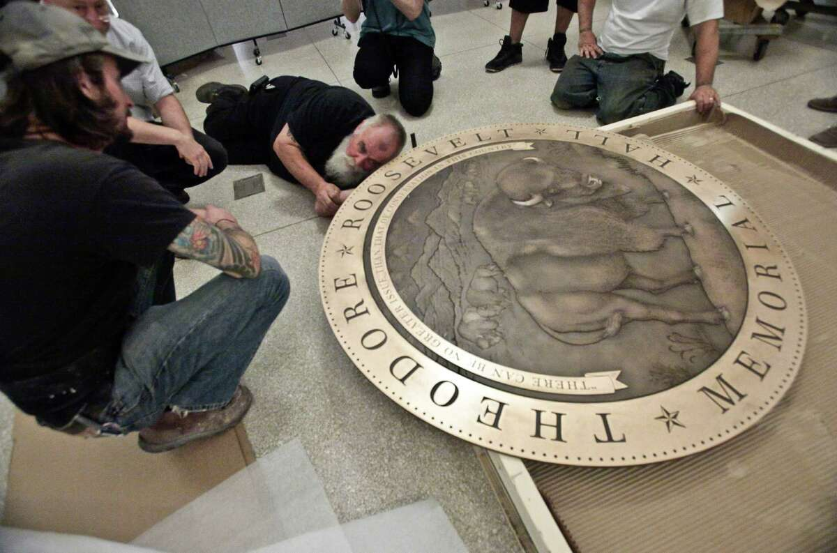 In this Thursday, Sept. 27, 2012 photo, workers prepare a floor medallion for the Theodore Roosevelt Memorial at the American Museum of Natural History in New York. The AMNH is reopening the two-story Theodore Roosevelt Memorial after a three-year, $42.1 million restoration project.