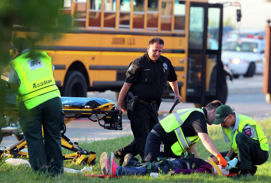 Police and paramedics prepare to transport a student after a San Antonio Independent School bus and a Judson Independent School District School bus collided on Foster road in front of Karen Wagner High School about 7:30 a.m. Monday October 1, 2012. The 60-year-old female bus driver of the SAISD bus died at the scene and three students were transported to area hospitals with minor injuries according to Bexar County Sheriff's Office Lt. Jose Trevino. Photo: John Davenport/Express-News