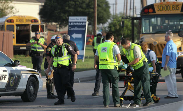 Police and paramedics prepare to transport an adult male after a San Antonio Independent School bus and a Judson Independent School District School bus collided on Foster road in front of Karen Wagner High School about 7:30 a.m. Monday October 1, 2012. The 60-year-old female bus driver of the SAISD bus died at the scene and three students were transported to area hospitals with minor injuries according to Bexar County Sheriff's Office Lt. Jose Trevino. Trevino said there were 40 students on the Judson bus and 5 students on the SAISD bus. Photo: John Davenport/Express-News