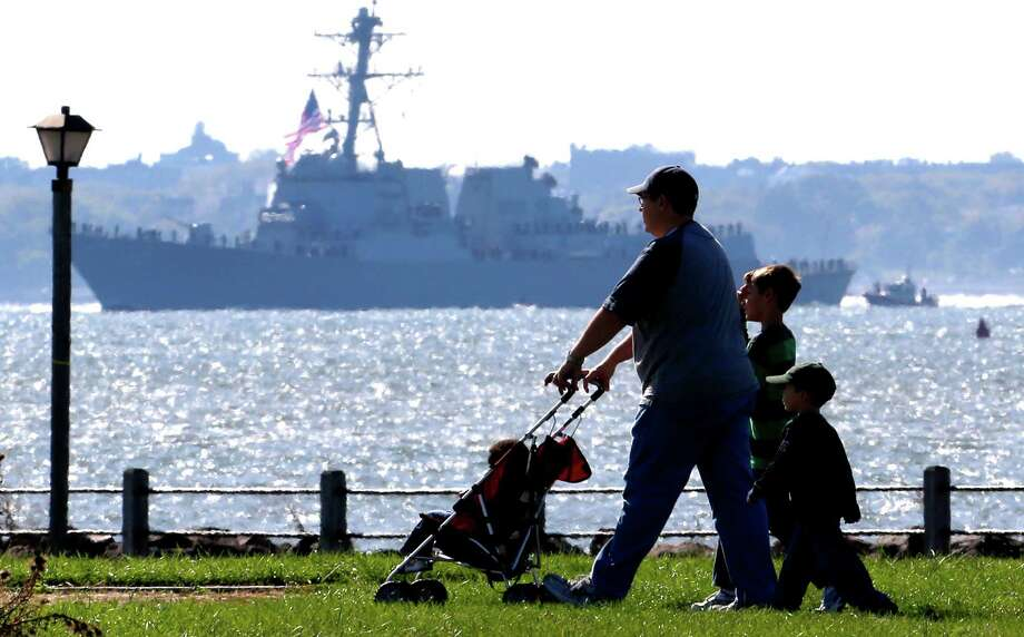 People walk on a path at Liberty State Park as the USS Michael Murphy, a new Navy destroyer named after Navy SEAL killed in Afghanistan, chugs along the Hudson River, Monday, OCt. 1, 2012, in Jersey City, N.J. Photo: Julio Cortez, Associated Press / AP