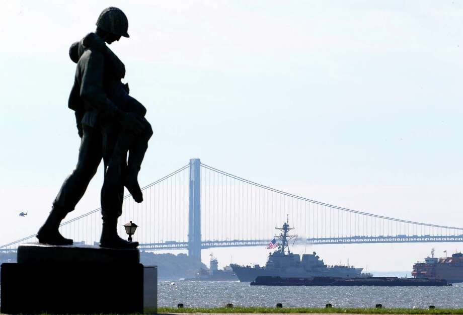 With a statue by Natan Rapoport depicting a soldier carrying a World War II concentration camp survivor in the foreground, the USS Michael Murphy, a new Navy destroyer named after a Navy SEAL killed in Afghanistan, chugs near the Verrazano Bridge, back, along the Hudson River, as seen from Liberty State Park, Monday, Oct. 1, 2012, in Jersey City, N.J. Lt. Michael P. Murphy was awarded the Medal of Honor for his actions in combat as leader of a four-man reconnaissance team in Afghanistan. The guided-missile destroyer is designed to counter threats from the air and sea, and from aircraft, ships and submarines. (AP Photo/Julio Cortez) Photo: Julio Cortez, Associated Press / AP