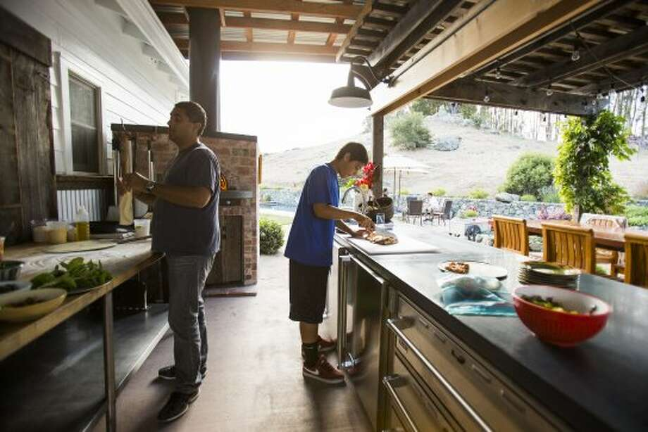 Chef Michael Mina, left, and son Sam make a pizza in their home's outdoor kitchen. (Stephen Lam / Special to The Chronicle)