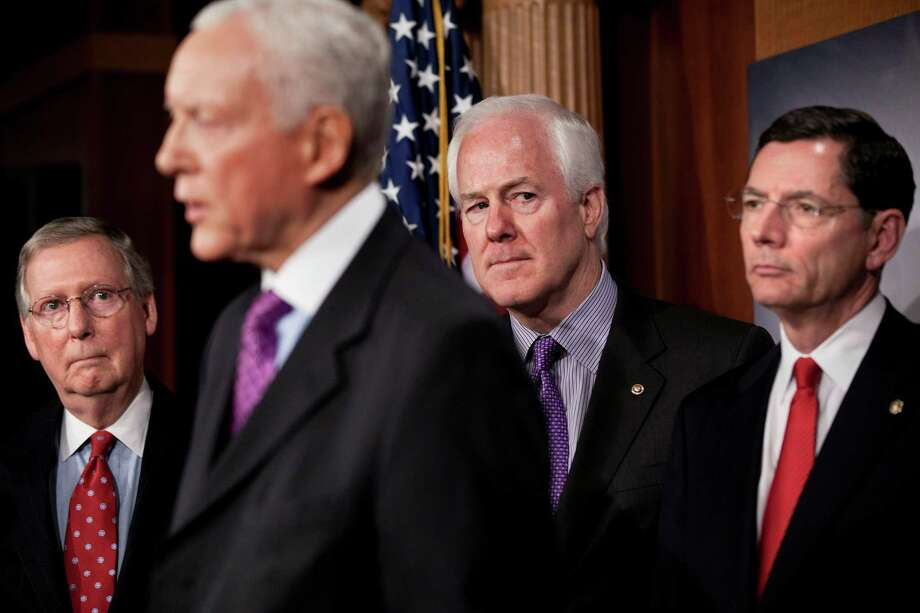 Senator John Cornyn, Senate Minority Leader Mitch McConnell, R-Ky., and Senator John Barrasso, R-Wyo., listen while Senator Orrin G. Hatch, R-Utah, speaks during a press conference on Capitol Hill Feb. 2, 2011 in Washington, DC. Photo: Brendan Smialowski, Getty Images / Getty Images North America