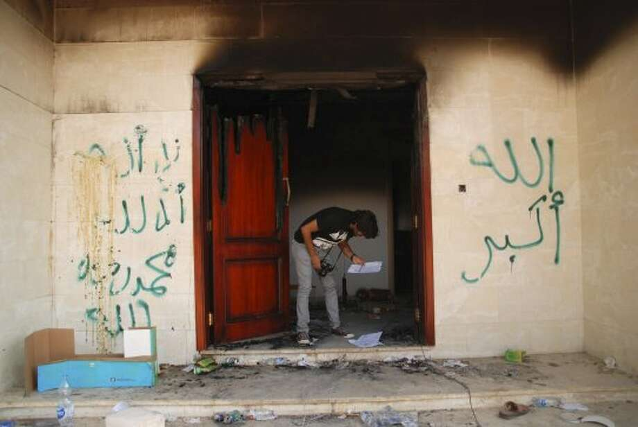 "A man looks at documents at the U.S. consulate in Benghazi, Libya, after an attack that killed four Americans, including Ambassador Chris Stevens, Wednesday, Sept. 12, 2012. The graffiti reads, ""no God but God,"""" God is great,"" and ""Muhammad is the Prophet."" The American ambassador to Libya and three other Americans were killed when a mob of protesters and gunmen overwhelmed the U.S. Consulate in Benghazi, setting fire to it in outrage over a film that ridicules Islam's Prophet Muhammad. Ambassador Chris Stevens, 52, died as he and a group of embassy employees went to the consulate to try to evacuate staff as a crowd of hundreds attacked the consulate Tuesday evening, many of them firing machine-guns and rocket-propelled grenades. (Ibrahim Alaguri / Associated Press)"