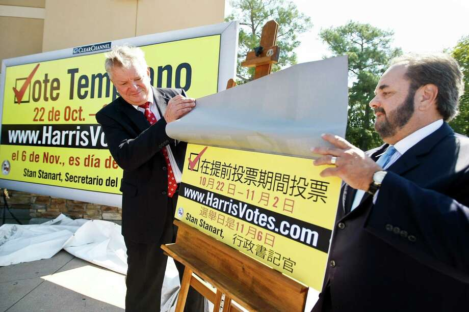Harris County Commissioner Steve Radack, left, and Lee Vela, of Clear Channel, unveil an example of an early voting billboard that's in Chinese during a press conference Monday, Oct. 1, 2012, in Houston. Clear Channel has donated space for billboards to be displayed county wide to promote early voting for the November 6, 2012 General & Special Elections. The billboards will be in English, Spanish, Vietnamese, and Chinese. Photo: Nick De La Torre, Houston Chronicle / © 2012  Houston Chronicle