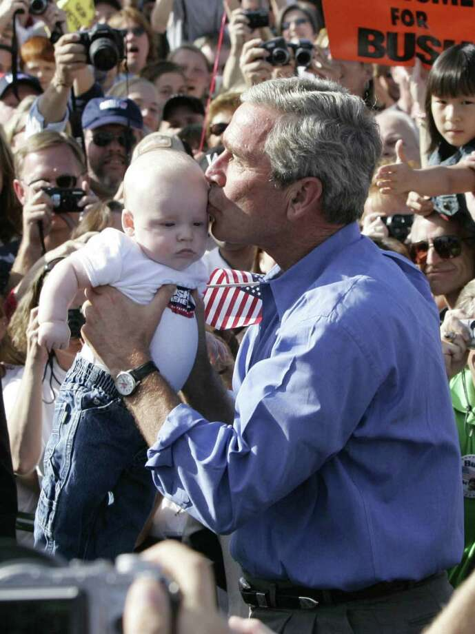 President George W. Bush kisses a baby as he arrives at an election rally in Chanhassen, Minn., Oct. 9, 2004.  REUTERS/Jason Reed Photo: Jason Reed/Reuters