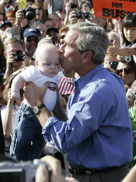 President George W. Bush kisses a baby as he arrives at an election rally in Chanhassen, Minn., Oct.
