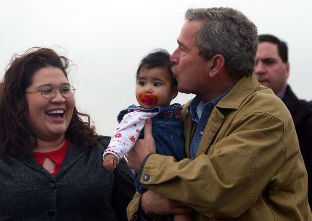President Bush kisses nine-month-old Liana Flores, as her mother Jackie looks on, after his arrival at Brooks County Airport in Falfurrias, Texas, Jan 1, 2004. (AP Photo/Susan Walsh) Photo: Susan Walsh/AP