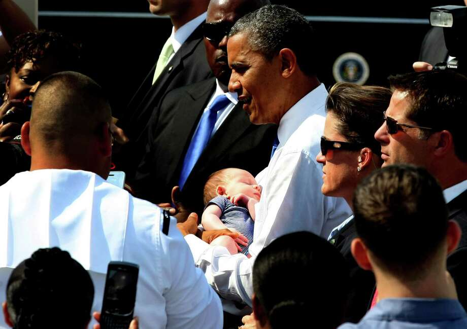 President Barack Obama holds a baby during a campaign stop, Thursday, Sept. 27, in Virginia Beach, Va. (AP Photo/Jason Hirschfeld) Photo: Jason Hirschfeld, Jason Hirschfield/AP