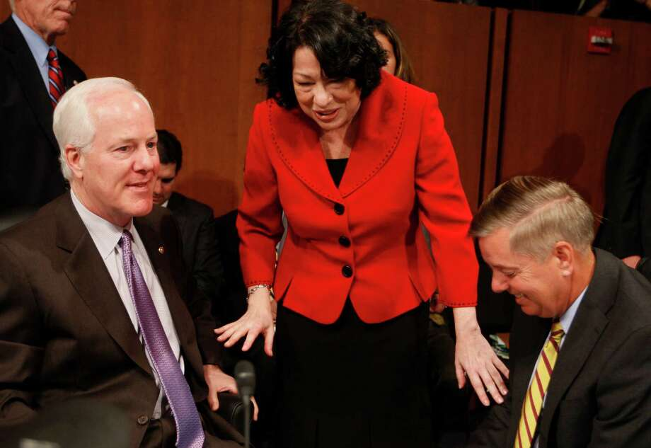 Supreme Court nominee Sonia Sotomayor talks with Sen. John Cornyn and Sen. Lindsey Graham, R-S.C. on Capitol Hill in Washington, Tuesday July 14, 2009, during a break in her confirmation hearing. Photo: Charles Dharapak, AP / AP