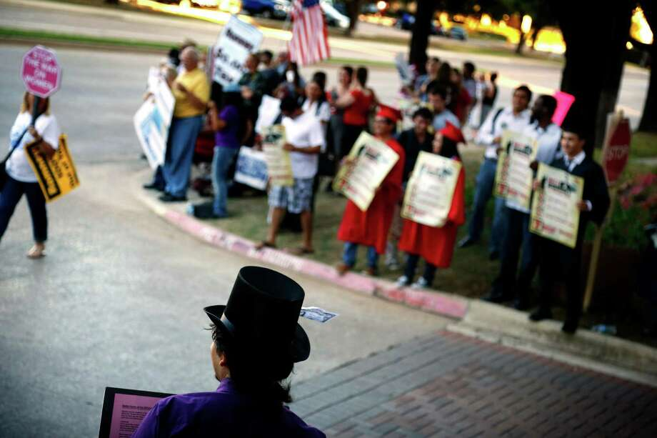 Protestors line the street and driveway leading to the Hilton Anatole hotel in Dallas, where Republican presidential candidate Mitt Romney is holding a private fundraiser, Tuesday, Sept. 18, 2012. Photo: Tom Fox, Associated Press / The Dallas Morning News