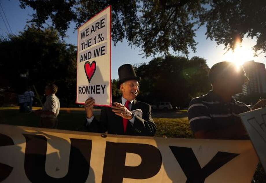 Occupy Dallas protestor Grant Youngman of Double Oak, Texas, center, protests Republican Presidential Candidate Mitt Romney  outside the Hilton Anatole hotel in Dallas as  Romney holds a private fundraiser  on Tuesday, Sept. 18, 2012.  (Tom Fox / Associated Press)