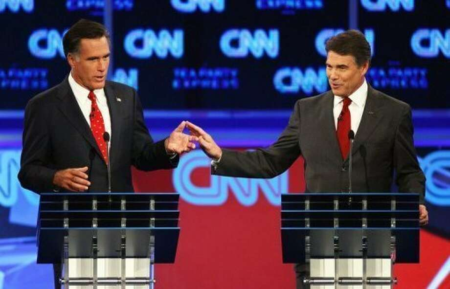 Rick Perry and Mitt Romney clash at a debate sponsored by CNN. (AFP photo)