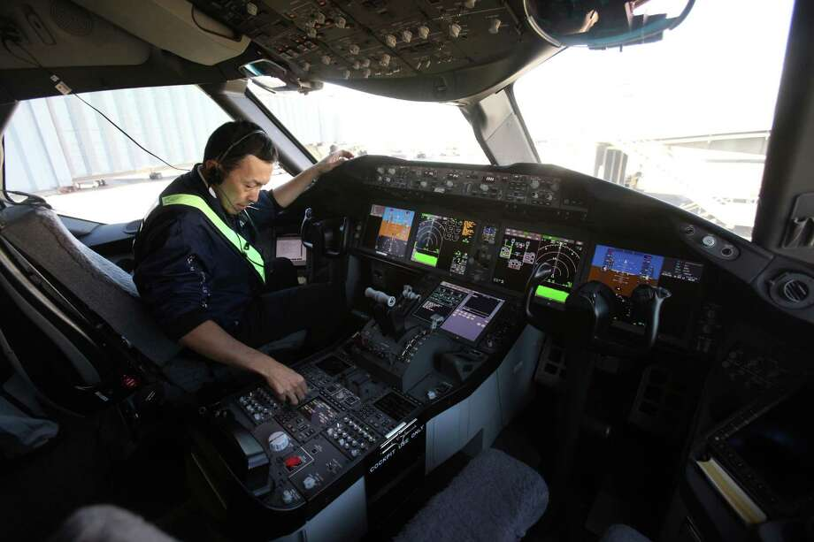 Maintenance employee Hisa Matsu works in the flight deck as a maintenance issue was discovered aboard the first Boeing 787 to provide commercial service to Sea-Tac Airport. Photo: JOSHUA TRUJILLO / SEATTLEPI.COM