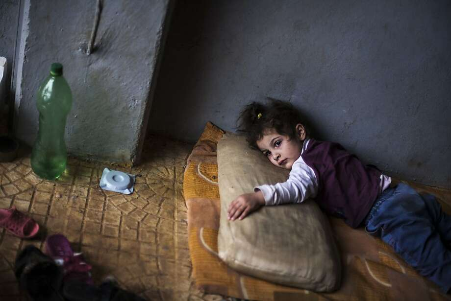 Rada Hallabi, 4, who is sick with diabetes, lies on a blanket  in a refugee camp on the border with Turkey, near Azaz village, Syria, Sunday, Sept. 30, 2012. (AP Photo / Manu Brabo) Photo: Manu Brabo, Associated Press