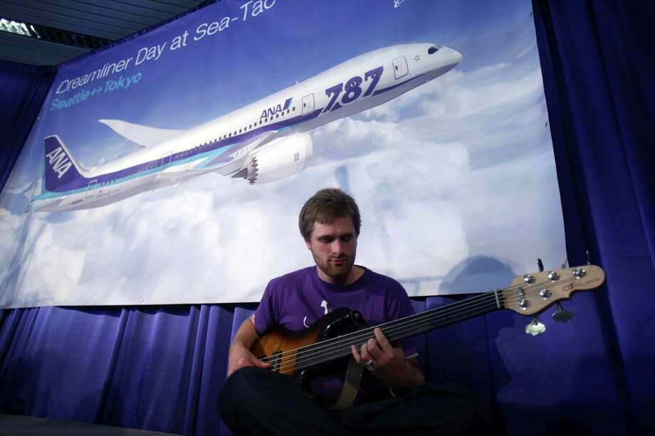 Passenger Dylan Hughes plays his bass as he waits to board first Boeing 787 to provide commercial service to Sea-Tac Airport. A delay was announced do to a mechanical problem with the aircraft. Hughes was on his way to Japan to get married. Photo: JOSHUA TRUJILLO / SEATTLEPI.COM