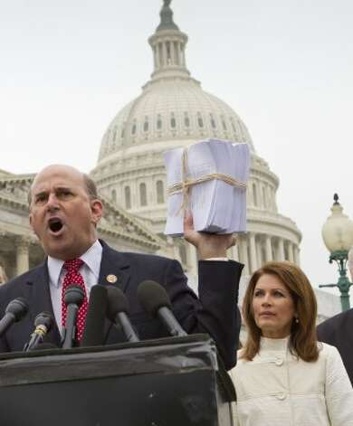 Rep. Louie Gohmert, R-Tyler, accompanied by Rep. Michele Bachmann, R-Minn., holds up a copy of the Patient Protection and Affordable Care Act, often referred to as Obamacare, during a a news conference on Capitol  Hill in Washington, Wednesday, March 21, 2012, to express their anger about the legislation on the second anniversary of its passage. (J. Scott Applewhite / Associated Press)