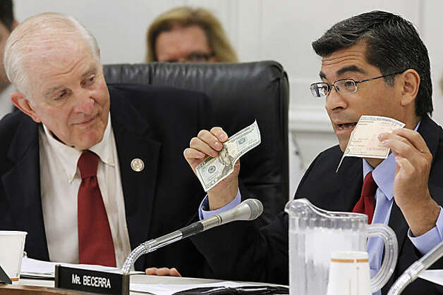 Rep. Sam Johnson, R-Plano, looks on as Rep. Xavier Becerra, D-Calif., holds a $20 bill and a savings bond, Capitol Hill in Washington, Friday, July 8, 2011, during the House Social Security Subcommittee's hearing on Social Security.  (Alex Brandon / The Associated Press)