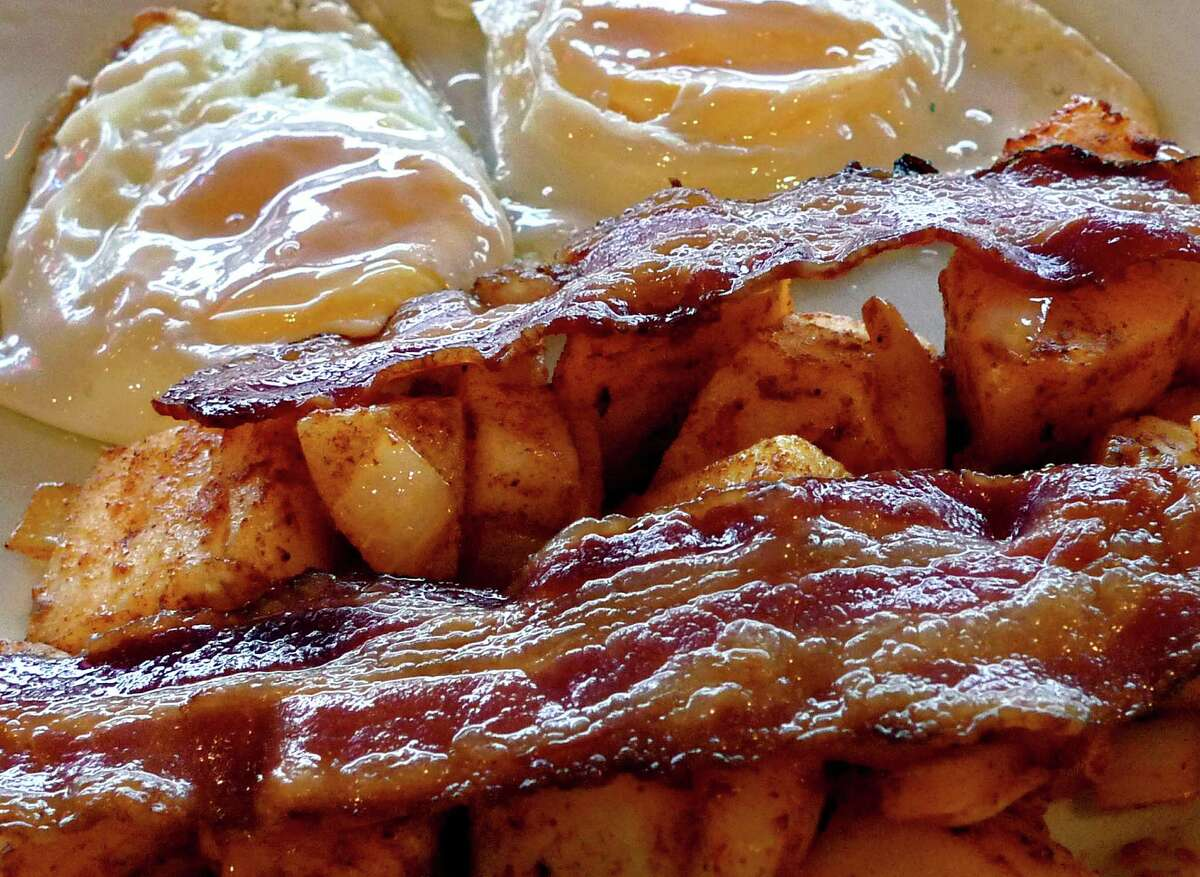 """Strips of sizzling bacon crown a breakfast platter with fried eggs and potatoes at a diner in Arlington, Va., Feb. 17, 2009. Fears about a scarcity of bacon on supermarket shelves due to last summer's drought are being dismissed as """"baloney"""" by the American Farm Bureau Federation, though consumers may see a price increase for bacon and other pork products. (AP Photo/J. Scott Applewhite)"""