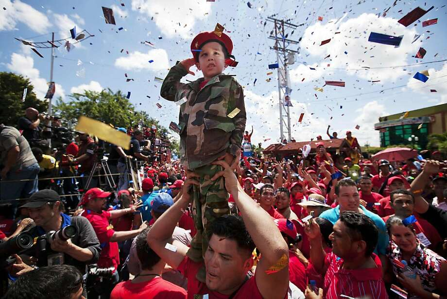 A boy dressed as a soldier salutes in Sabaneta, Venezuela, during a campaign visit by President Hugo Chavez. The incumbent is tied in the polls with challenger Henrique Capriles. Photo: Rodrigo Abd, Associated Press