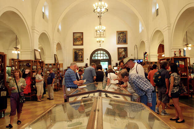 Customers view the artifacts display cases at the Alamo gift shop, Monday, Oct. 1, 2012. Event Network, which manages gift shops at several historical sites nationally, has taken over the Alamo gift shop starting Monday. The General Land Office hired the firm. GLO took over the management of the Alamo from the Daughters of the Republic of Texas. Photo: Jerry Lara, San Antonio Express-News / © 2012 San Antonio Express-News
