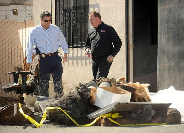 Vallejo police Lt. Jim O'Connell, left, lead investigator into a fire that blazed through Mayor Osby Davis' law office Saturday, inspects damaged material behind the building on Monday, Oct. 1, 2012, in Vallejo, Calif. Photo: Noah Berger, Special To The Chronicle