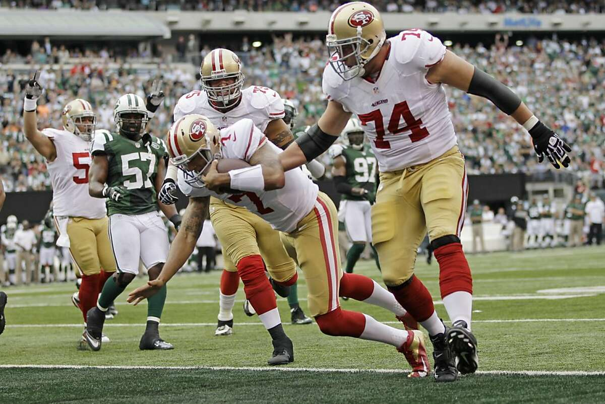 San Francisco 49ers quarterback Colin Kaepernick (7) rushes for a touchdown during the first half of an NFL football game as New York Jets inside linebacker Bart Scott (57) looks on Sunday, Sept. 30, 2012, in East Rutherford, N.J. (AP Photo/Kathy Willens)