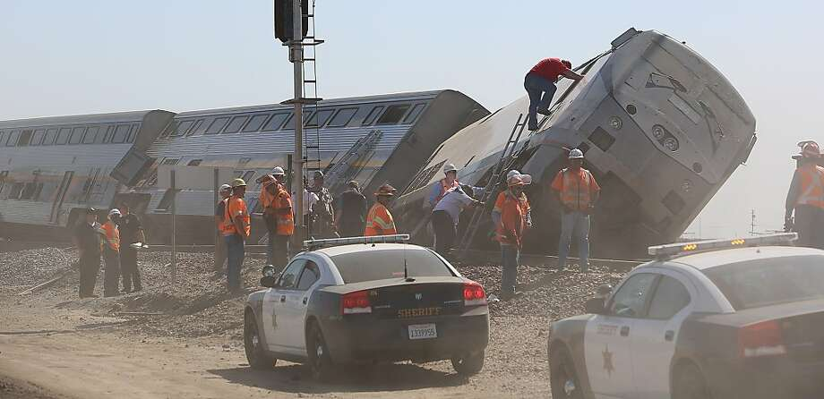 Emergency personnel respond to the scene of a train derailment where authorities say at least 20 passengers suffered minor to moderate injuries when a big rig truck collided with a southbound Amtrak train in the central valley Monday, Oct. 1, 2012 in Hanford, Calif.  (AP Photo/The Fresno Bee, Gary Kazanjian) Photo: Gary Kazanjian, Associated Press