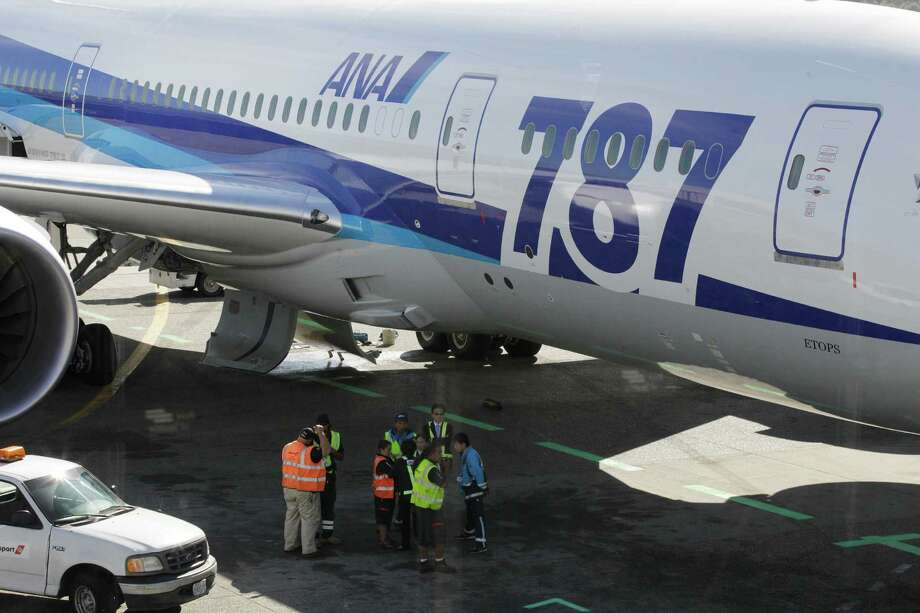 Ramp workers stand near a Boeing 787 operated by All Nippon Airways during a maintenance delay at Seattle-Tacoma International Airport, Monday, Oct. 1, 2012, on the first day of service for the 787 on ANA's Seattle-Tokyo route. Photo: Ted S. Warren, AP / AP