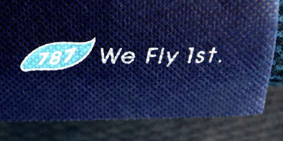 "The words ""787 We Fly 1st"" are shown on a seat in the economy class section of a Boeing 787 operated by All Nippon Airways, at Seattle-Tacoma International Airport, Monday, Oct. 1, 2012, on the first day of service for the 787 on ANA's Seattle-Tokyo route. After an official welcoming ceremony, the flight was delayed due to a maintenance issue. Photo: Ted S. Warren, AP / AP"