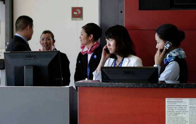 All Nippon Airways workers confer at the boarding gate for the first Seattle-Tokyo flight on a Boeing 787, at Seattle-Tacoma International Airport, Monday, Oct. 1, 2012. After an official welcoming ceremony, the flight was delayed 24 hours due to a maintenance issue. Photo: Ted S. Warren, AP / AP