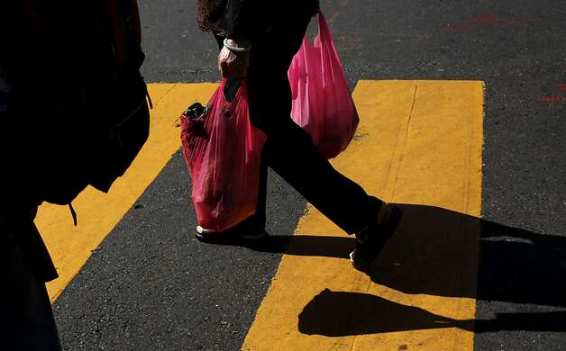 Some shoppers continued to take advantage of existing supplies of plastic, left. Photo: Sarah Rice, Special To The Chronicle