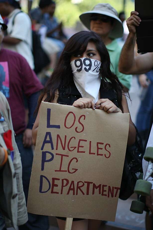 LOS ANGELES, CA - OCTOBER 1:  A protester holds a sign during a rally in the downtown financial district to mark the one-year anniversary of the Occupy movement on October 1, 2012 in Los Angeles, California. Inspired by Occupy Wall Street movement protests in New York, hundreds of Los Angeles demonstrators seized City Hall park last year and lived there for weeks until they were evicted in a dramatic police raid on the night of November 30, 2011.     (Photo by David McNew/Getty Images) Photo: David McNew, Getty Images