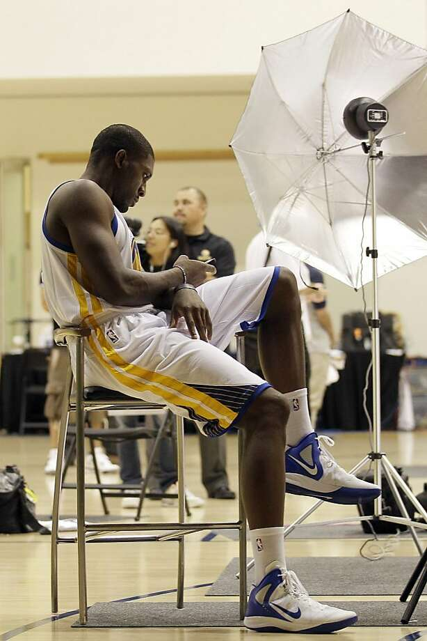 Golden State Warriors' Festus Ezeli, from Nigeria, uses his phone during their NBA basketball media day at the team's training facility in Oakland, Calif., Monday, Oct. 1, 2012. (AP Photo/Jeff Chiu) Photo: Jeff Chiu, Associated Press