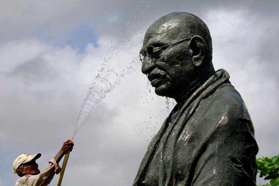 "A worker sprays water on a statue of the late Mahatma Gandhi on the eve of his birth anniversary at Gandhi Park in Bhubaneswar, eastern India, Monday, Oct. 1, 2012. Gandhi, known as the ""Father of the Nation,"" was instrumental in the movement that lead to India's independence from Britain in 1947. (AP Photo/Biswaranjan Rout) Photo: Biswaranjan Rout, Associated Press / AP"