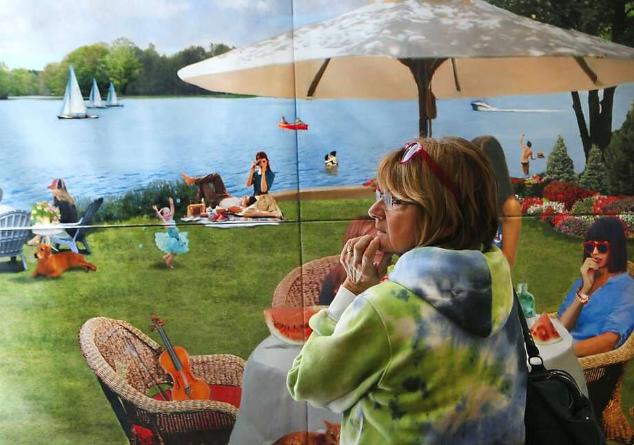 "Connie Uithol of Manton looks at ""Luncheon by the Lake,"" by Brad Deveaux, Monday, Oct. 1, 2012 at the Amway Grand Plaza in Grand Rapids, Mich. Uithol was visiting ArtPrize on a day trip with her daughter. (AP Photo/The Grand Rapids Press, Emily Zoladz) Photo: Emily Zoladz, Associated Press"