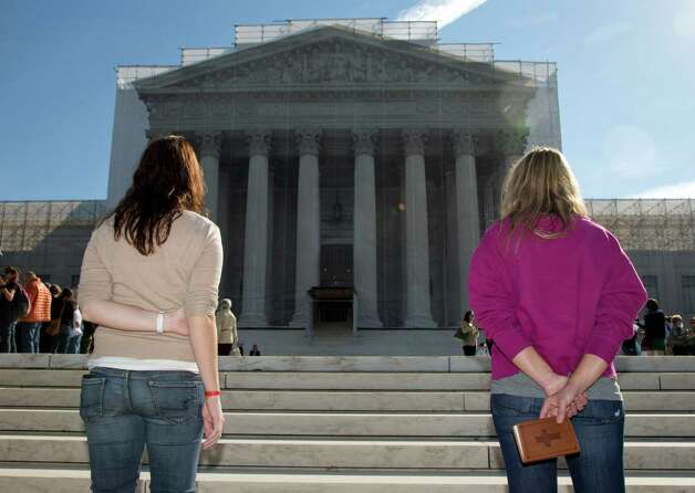 Women pray on the front steps of the Supreme Court in Washington, Monday, Oct. 1, 2012. The Supreme Court is embarking on a new term that could be as consequential as the last one with the prospect for major rulings about affirmative action, gay marriage and voting rights. (AP Photo/Carolyn Kaster) Photo: Carolyn Kaster