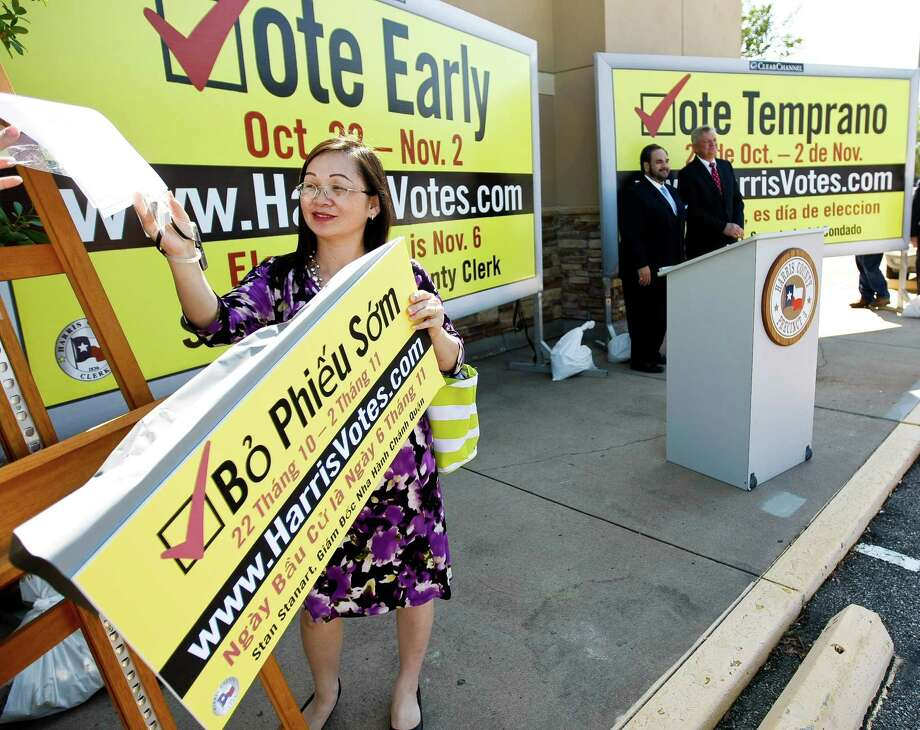 Duha Nguyen, a voter outreach coordinator with Harris County, picks up an example of an early voting billboard after a press conference unveiling the billboards Monday, Oct. 1, 2012, in Houston. Clear Channel has donated space for billboards to be displayed county wide to promote early voting for the November 6, 2012 General & Special Elections. The billboards will be in English, Spanish, Vietnamese, and Chinese. ( Nick de la Torre / Houston Chronicle ) Photo: Nick De La Torre / © 2012  Houston Chronicle