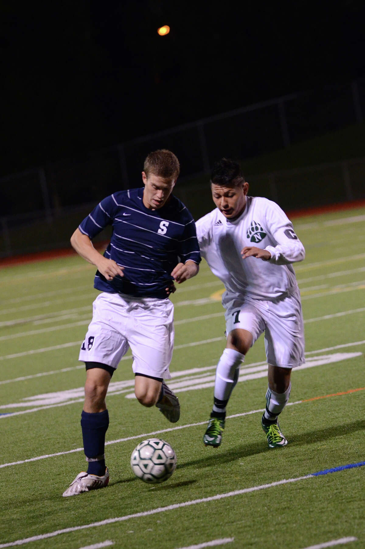 Staples' Ethan Bradeen (18) and Norwalk's Alejandro Rivera (7) battle for control of the ball during the boys soccer game at Norwalk High School's Testa Field on Monday, Oct. 1, 2012.