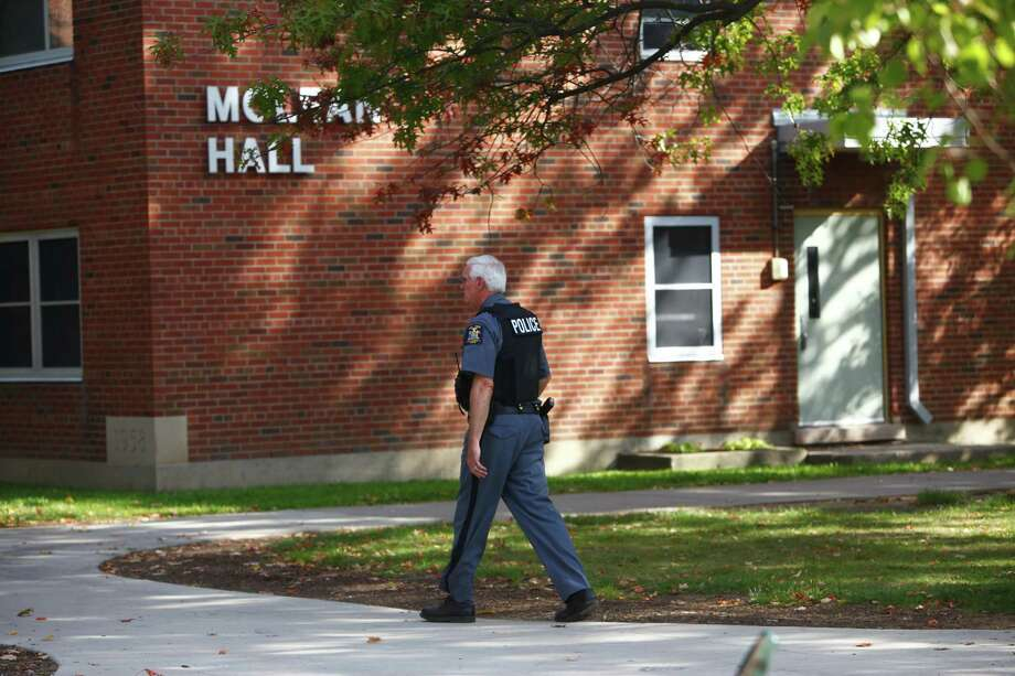 A New York State University police officer walks by McLean Hall at the State University of New York College at Brockport, which is the dormitory where female student Alexandra Kogut was found dead early Saturday, Sept. 29, 2012. About an hour later, police arrested her boyfriend at a Thruway rest stop near Syracuse. Authorities have charged 21-year-old Clayton Whittemore of New Hartford with second-degree murder. He has pleaded not guilty to the charge   (AP Photo/Democrat & Chronicle, Marie De Jesus)  MAGS OUT; NO SALES Photo: Marie De Jesus